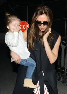 Victoria Beckham Carries Daugther Harper As They Arrive at LAX With Her Sons