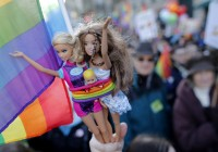 A demonstrator holds Barbie dolls as people march through the streets of Paris in support of the French government's draft law to legalise marriage and adoption for same-sex couples